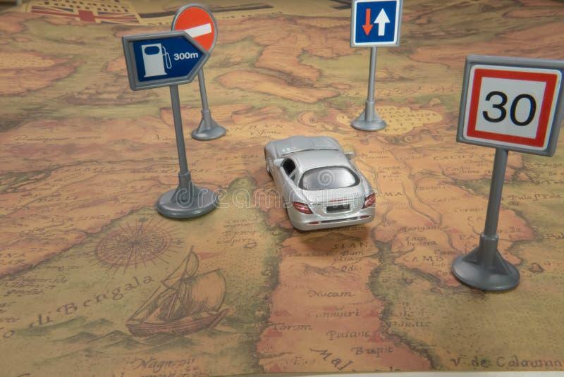 concepto del recorrido Coche del juguete en mapa del mundo del vintage con la señal de tráfico foto de archivo libre de regalías