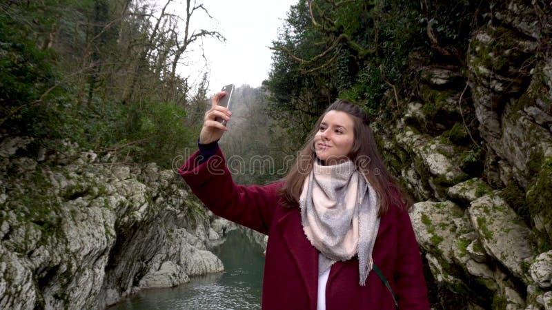concepto del recorrido Mujer que toma el selfie en la puerta del diablo del barranco en Sochi, Rusia imagenes de archivo