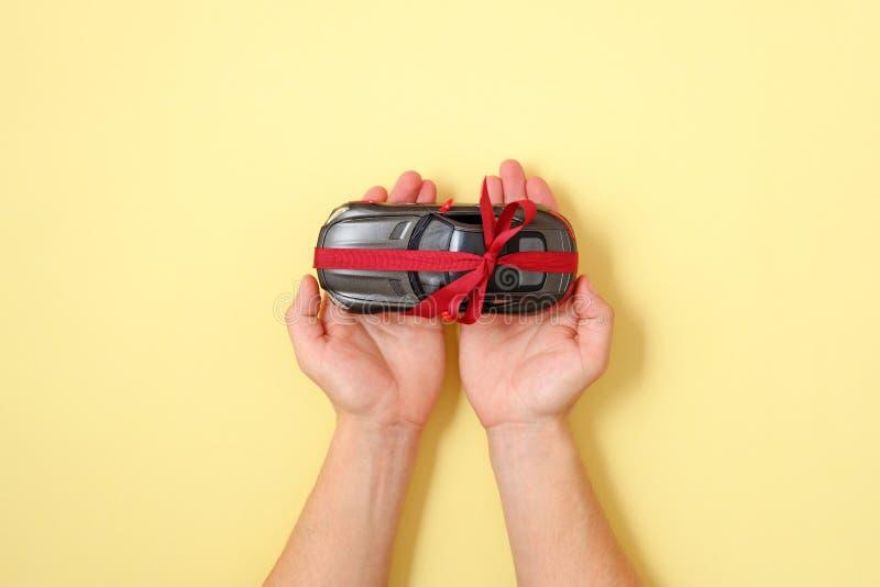 Concepto del regalo del coche Tenencia humana en manos en el coche del juguete de la palma con la cinta roja en fondo amarillo Vi foto de archivo libre de regalías