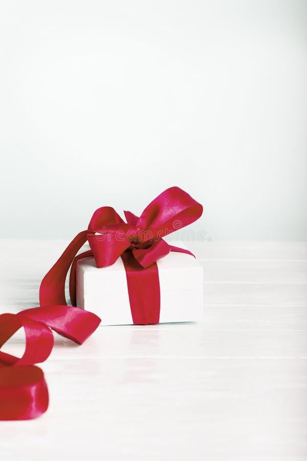 Concepto del regalo de Navidad del cumpleaños del regalo - caja de regalo blanca con re foto de archivo libre de regalías