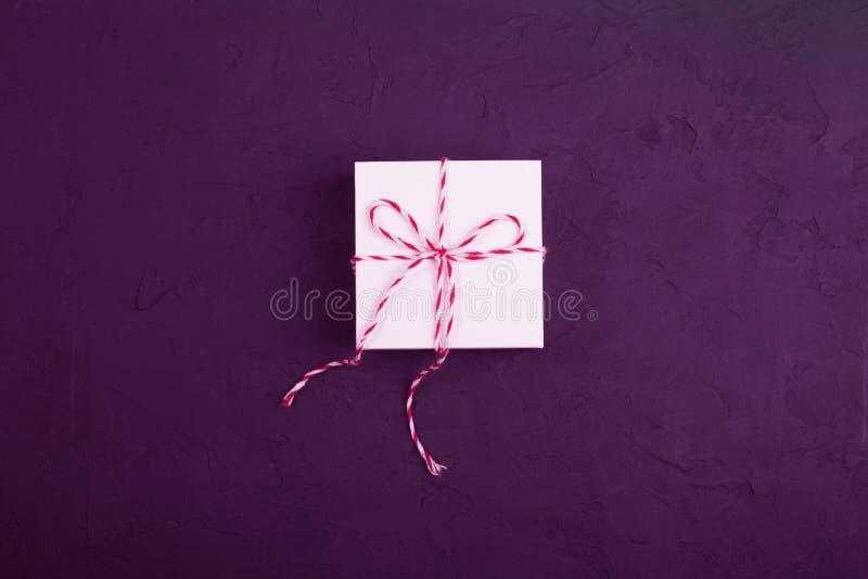 Concepto del regalo de Navidad - la caja de regalo blanca con guita acuñó encendido foto de archivo