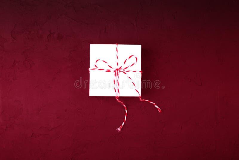 Concepto del regalo de Navidad - la caja de regalo blanca con guita acuñó o foto de archivo