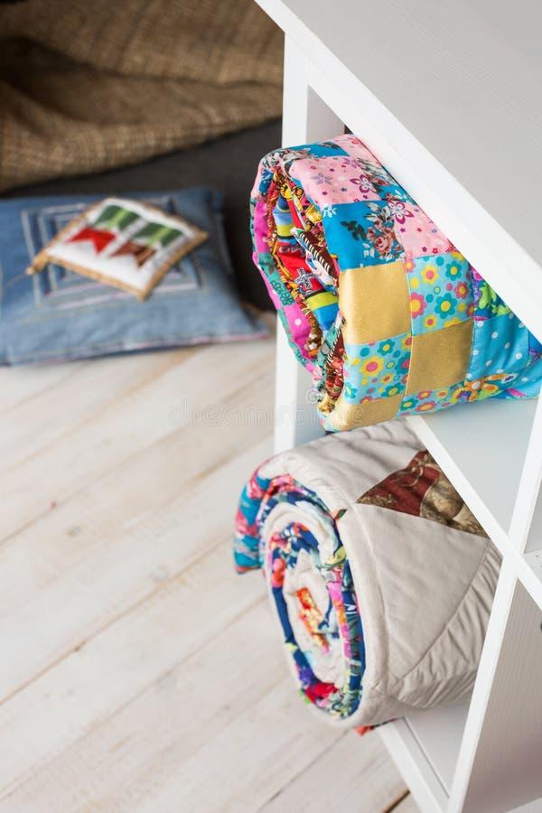 Concepto del remiendo, de la costura y de la moda - dos colchas acolchadas coloridas en estudio en los estantes blancos con pocos foto de archivo