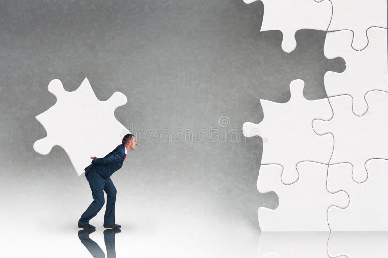 Concepto del rompecabezas del negocio con el hombre de negocios y el rompecabezas imagen de archivo libre de regalías
