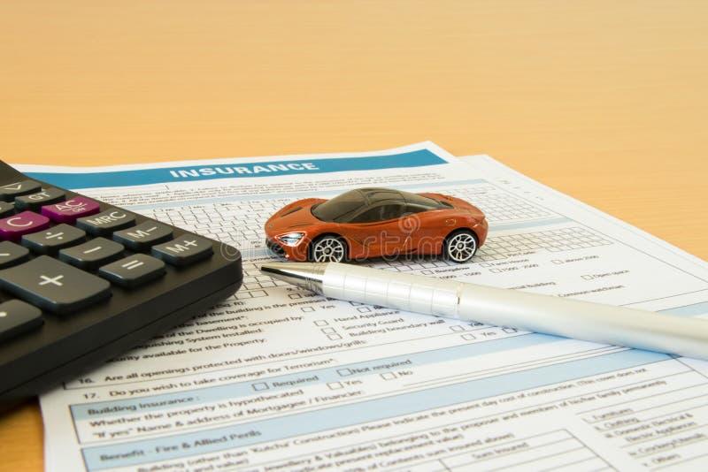 Concepto del seguro de coche con la forma del seguro, el coche miniatura, la calculadora y la pluma en un fondo de madera ligero fotografía de archivo