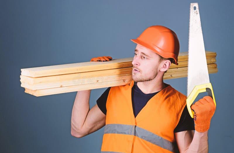 Concepto del sentido de la orientación El carpintero, carpintero, trabajador, constructor en cara pensativa lleva haces de madera foto de archivo