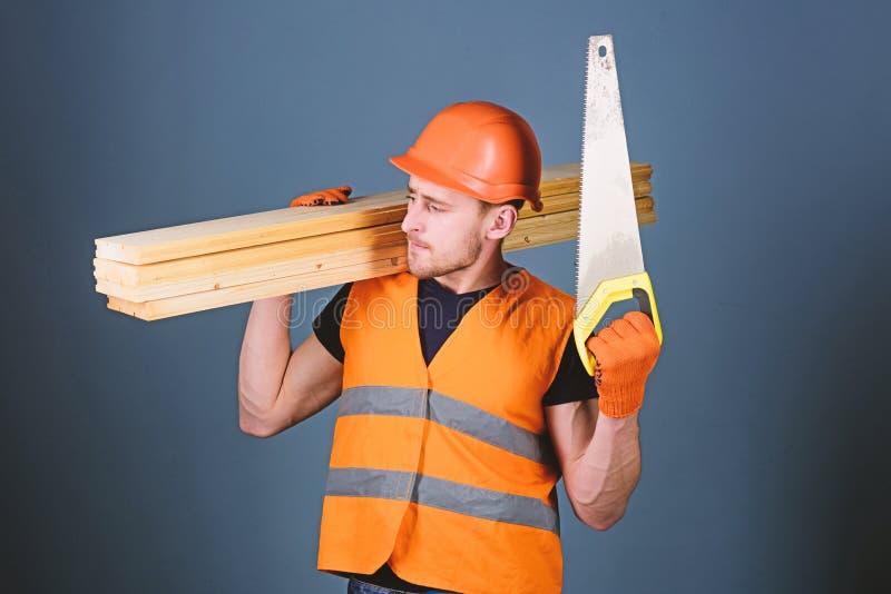 Concepto del sentido de la orientación El hombre, manitas en el casco, casco lleva a cabo el handsaw y los haces de madera, fondo imágenes de archivo libres de regalías