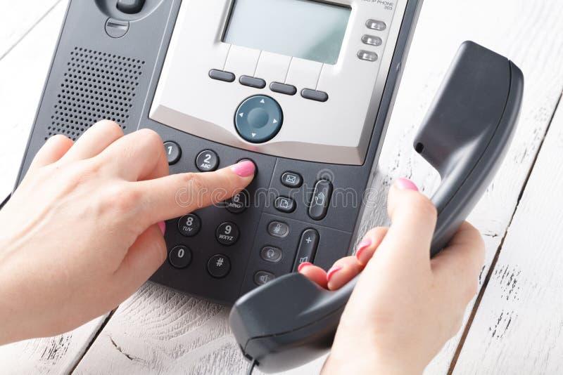 Concepto del teléfono del centro de atención telefónica o de la oficina, número femenino de la prensa del finger en phonepad imágenes de archivo libres de regalías