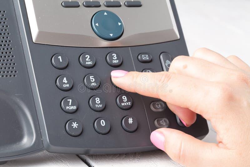 Concepto del teléfono del centro de atención telefónica o de la oficina, número femenino de la prensa del finger en phonepad imagenes de archivo