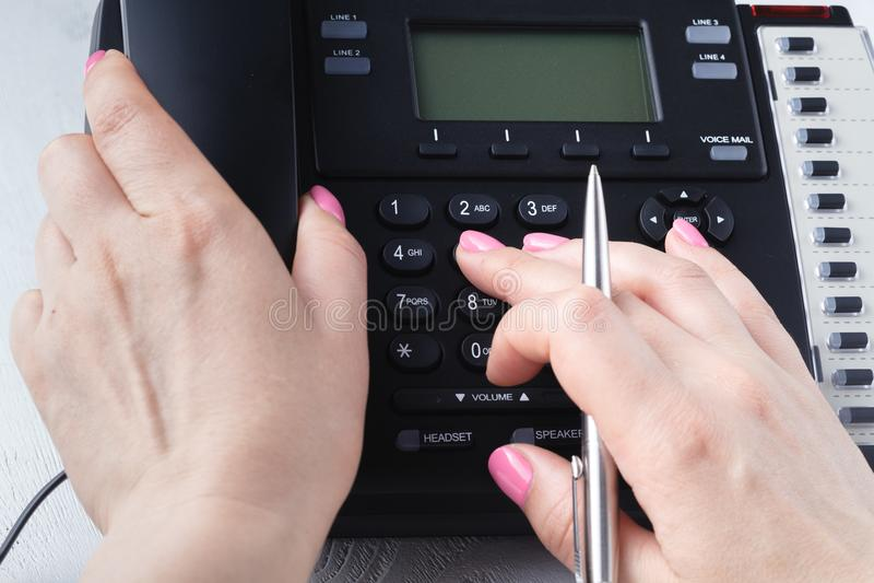 Concepto del teléfono del centro de atención telefónica o de la oficina, número femenino de la prensa del finger en phonepad fotografía de archivo