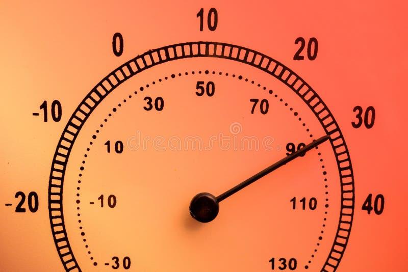 Concepto del tiempo caliente Cara del termómetro de la aguja con temperatura alta Escala en Celsius y Fahrenheit Color encendido  fotografía de archivo
