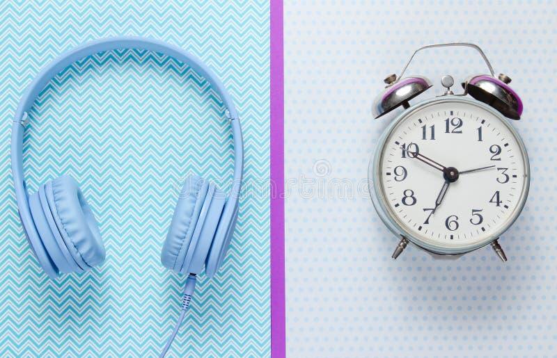 Concepto del tiempo de la m?sica Despertador y auriculares retros en fondo creativo Visi?n superior imagenes de archivo