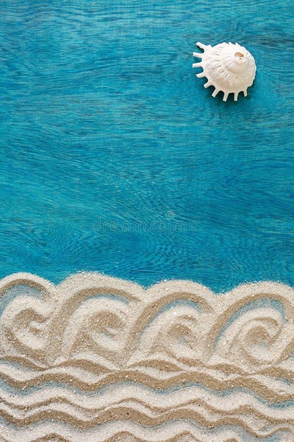 Concepto del tiempo de verano con la arena del diseño y solas cáscaras del mar como SOL en un fondo de madera azul, visión superi fotografía de archivo libre de regalías