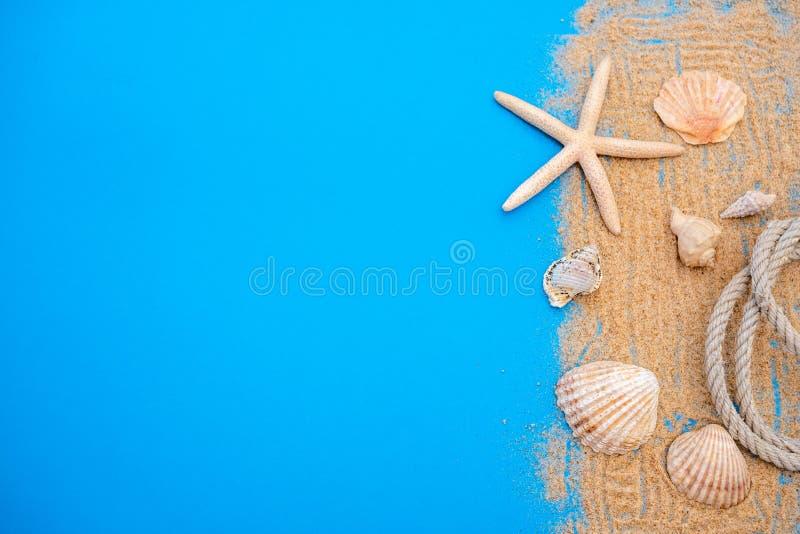 Concepto del tiempo de verano con las cáscaras y las estrellas de mar del mar en un fondo y una arena de madera azules foto de archivo libre de regalías