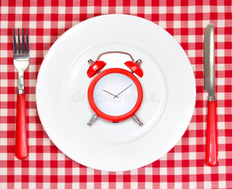 Concepto del tiempo del almuerzo de la dieta Despertador rojo en la placa blanca redonda imágenes de archivo libres de regalías
