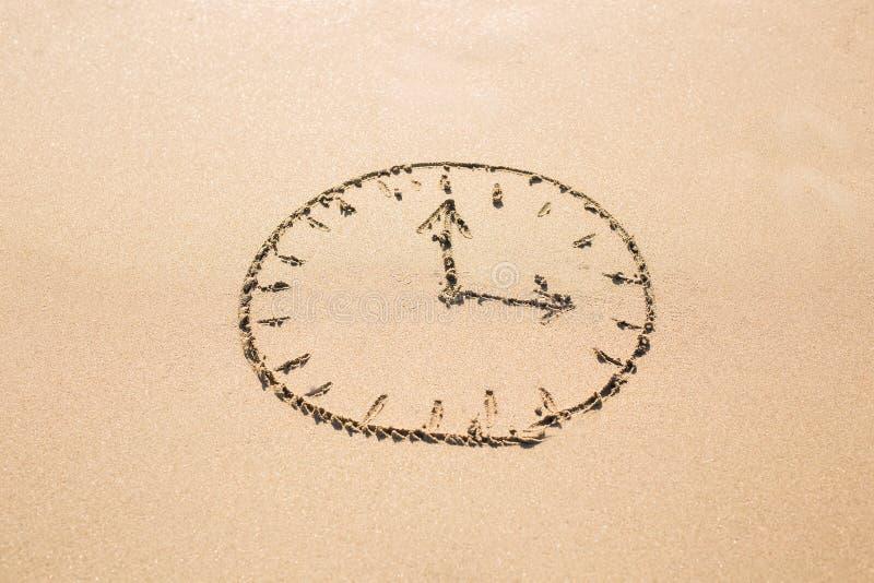 Concepto del tiempo - imagen de una cara de reloj en la playa arenosa foto de archivo libre de regalías