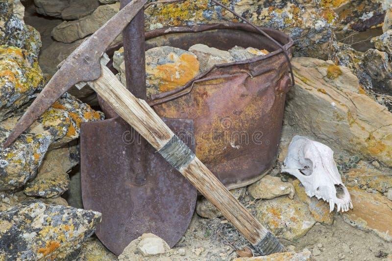 Concepto del trabajo del cráneo de las rocas de la pala del cubo de la selección de los mineros imagen de archivo libre de regalías