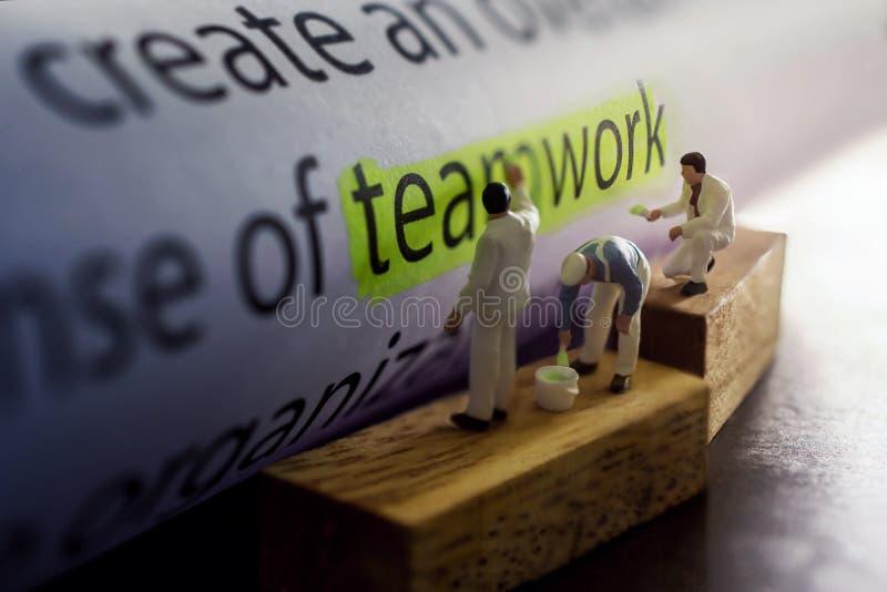 Concepto del trabajo en equipo del asunto Grupo de figura miniatura que pinta a GR foto de archivo