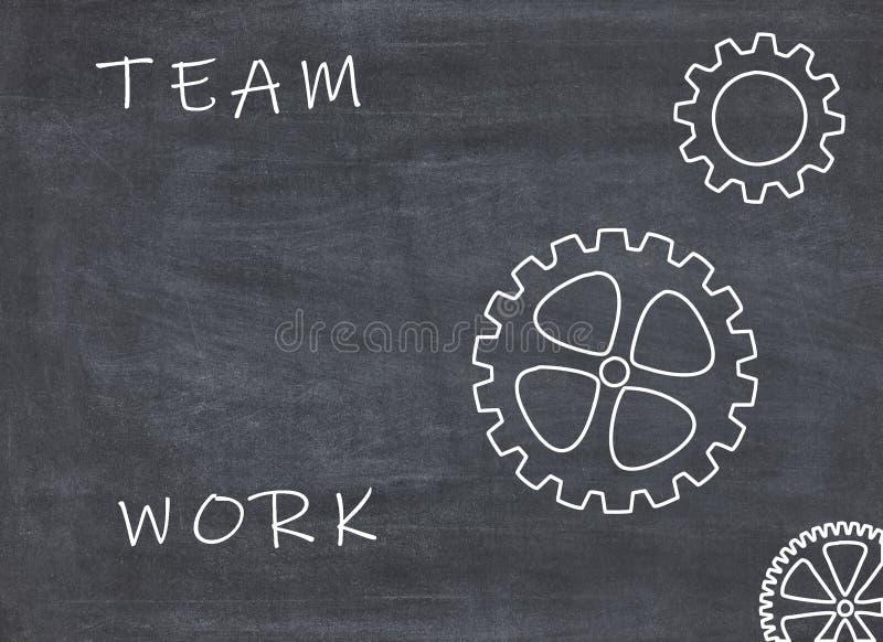 Concepto del trabajo en equipo con las ruedas dentadas y el texto en fondo de la pizarra imagen de archivo