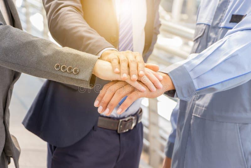 Concepto del trabajo en equipo del éxito, hombres de negocios que se unen a al CCB de la ciudad de las manos foto de archivo libre de regalías