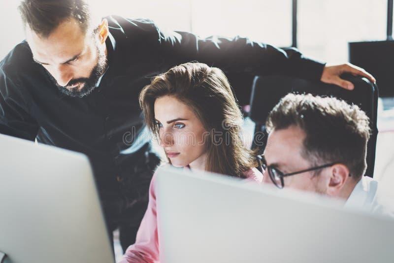 Concepto del trabajo en equipo Los compañeros de trabajo jovenes que trabajan con nuevo negocio proyectan en oficina moderna El g imagen de archivo libre de regalías