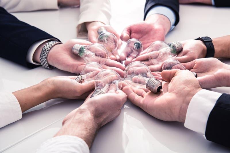 Concepto del trabajo en equipo y de la reunión de reflexión con los hombres de negocios que comparten una idea con una lámpara Co imagen de archivo libre de regalías