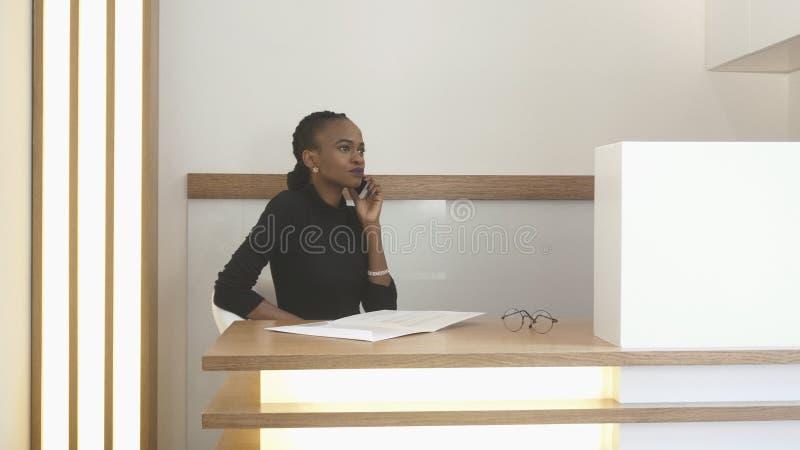 Concepto del trabajo Mujer de Africna en el receprion La mujer encantadora atractiva con maquillaje natural está hablando con imagen de archivo libre de regalías
