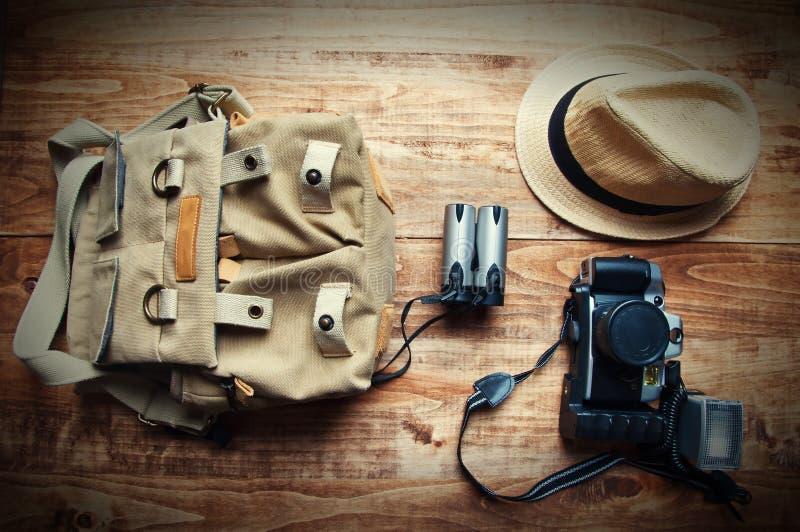 Concepto del turismo Isolat de la mochila, del sombrero, binocular y viejo de la cámara fotografía de archivo