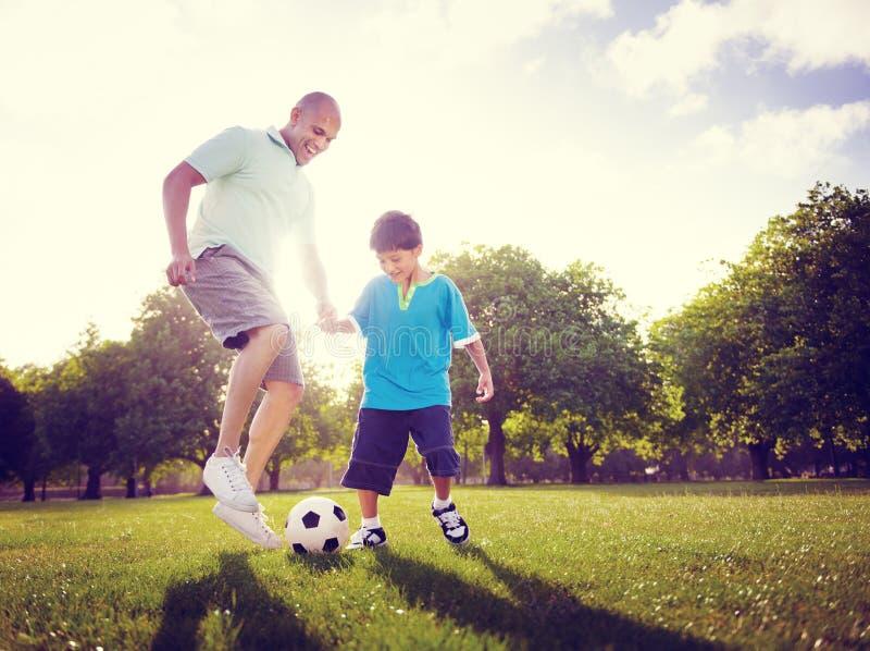 Concepto del verano de Son Playing Football del padre de la familia fotos de archivo