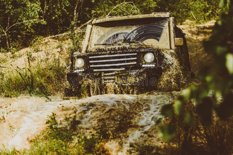 Concepto del viaje con el coche grande 4x4 Pista en fango coche campo a trav?s del suv 4x4 Coche campo a trav?s safari Chapoteo d imagen de archivo