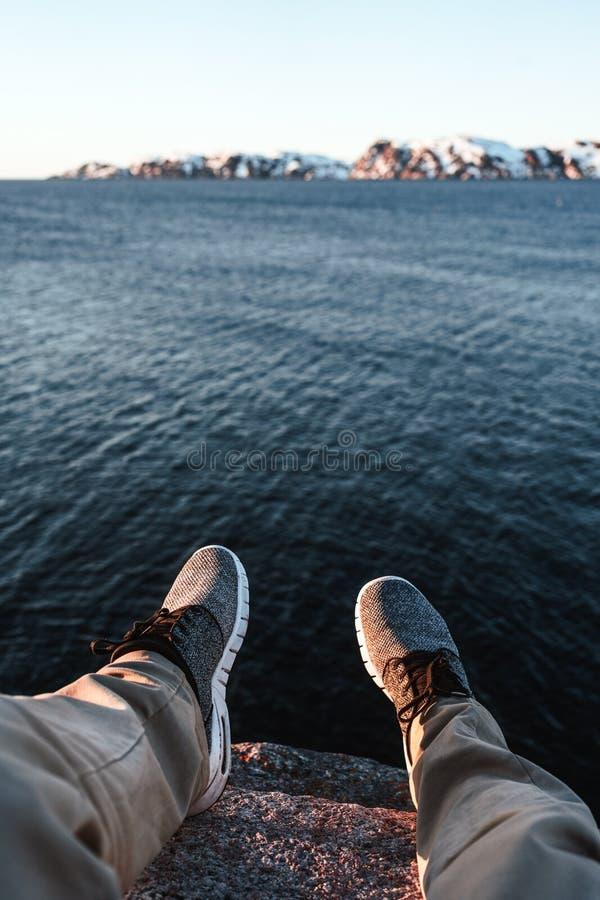 Concepto del viaje y de la forma de vida El inconformista valiente del viajero se sienta en el acantilado delante del océano y de fotos de archivo libres de regalías
