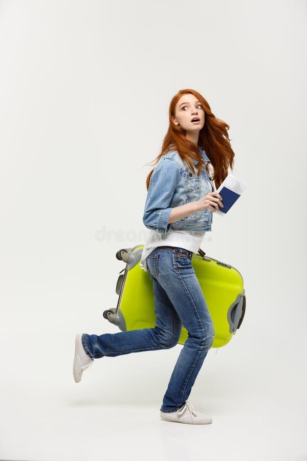 Concepto del viaje y de la forma de vida - mujer del retrato que se sostiene y que corre con una maleta y un pasaporte grandes pa fotos de archivo