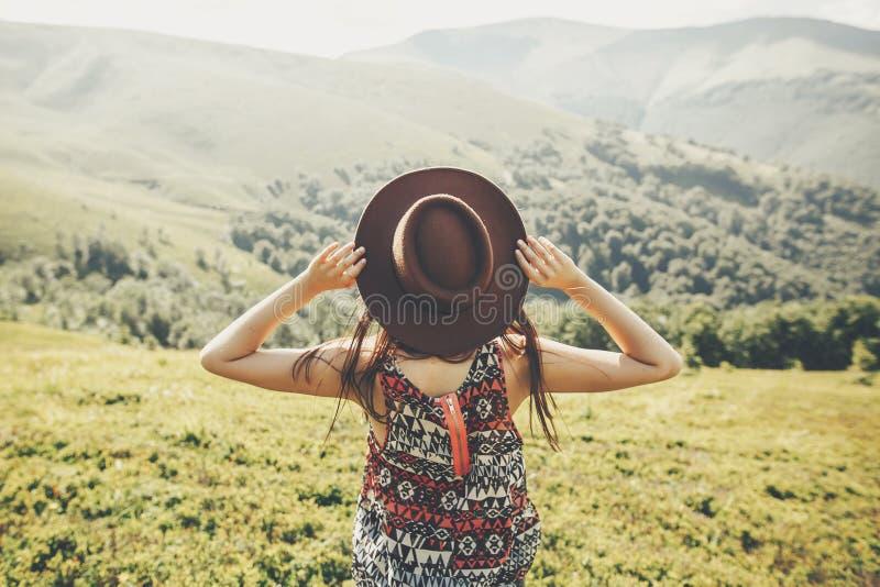 concepto del viaje y de la pasión por los viajes muchacha del inconformista del viajero que sostiene el sombrero imágenes de archivo libres de regalías