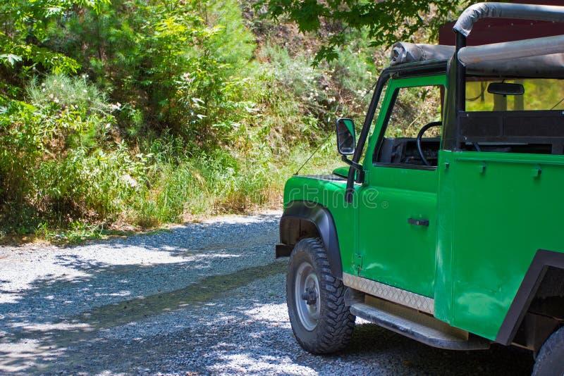 Concepto del viaje y de las vacaciones - coche del safari en bosque foto de archivo
