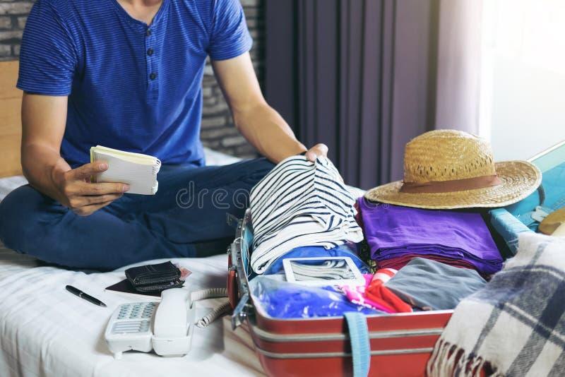 Concepto del viaje y de las vacaciones, hombre joven de la felicidad que embala mucho o imagen de archivo libre de regalías
