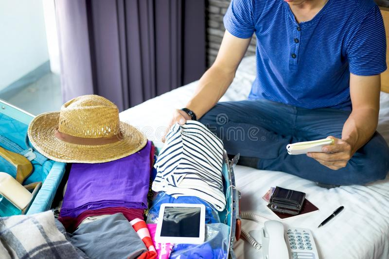 Concepto del viaje y de las vacaciones, hombre joven de la felicidad que embala mucho o fotografía de archivo