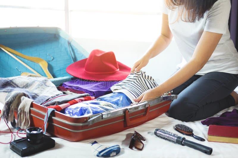 Concepto del viaje y de las vacaciones, mujer joven de la felicidad que embala mucho fotografía de archivo