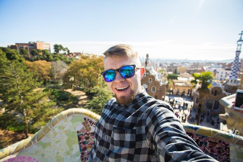 Concepto del viaje y de los días de fiesta - individuo feliz que hace el retrato del selfie con smartphone en el parque Guell, Ba imagen de archivo libre de regalías