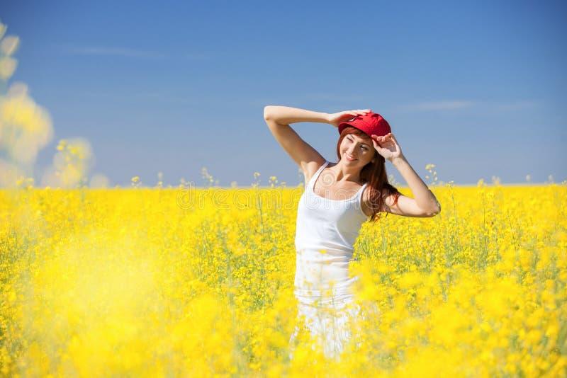 Concepto del ?xito de la libertad de la gente Mujer feliz en el campo con las flores en el d?a soleado en el campo Fondo de la be fotos de archivo libres de regalías