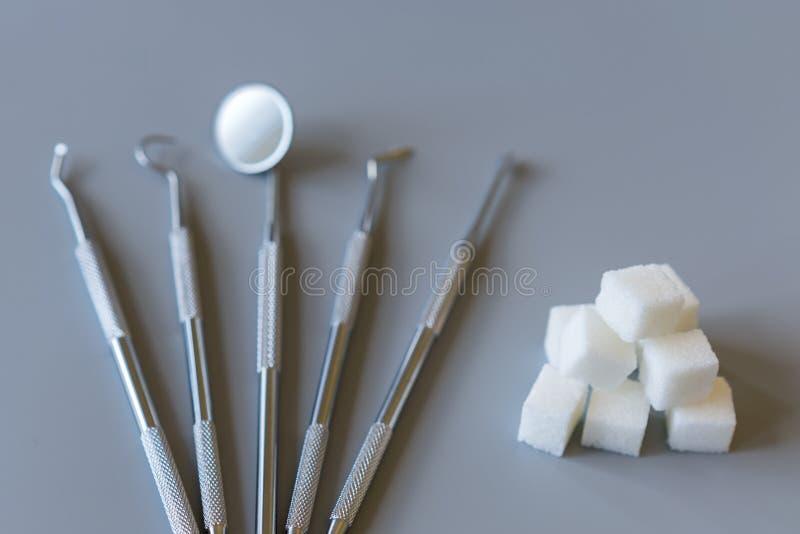Concepto dental del tratamiento opción dulce o del dentista Herramientas y azúcar dentales en un fondo gris foto de archivo
