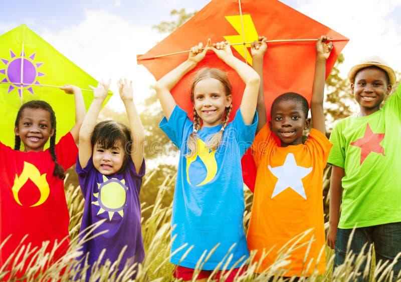 Concepto diverso de los jóvenes del campo de la cometa de los niños que juega foto de archivo libre de regalías