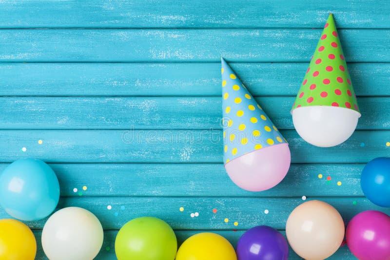 Concepto divertido del cumpleaños Globos coloridos con los casquillos y confeti en la opinión de sobremesa de la turquesa Fondo d imagenes de archivo