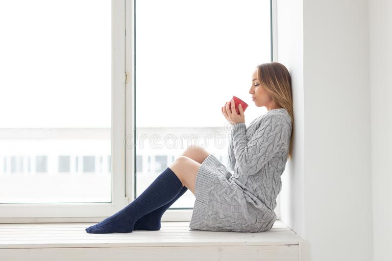 Concepto el esperar, de la soledad y de la belleza - mujer joven en vestido de las lanas con la taza de té caliente que se sienta fotos de archivo libres de regalías