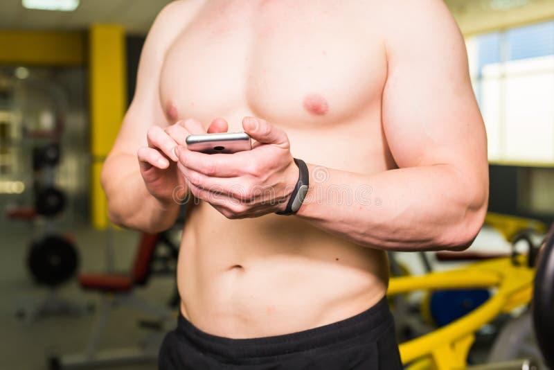 Concepto elegante de la aptitud del entrenamiento Primer del atleta muscular joven que comprueba programa de entrenamiento sobre  fotos de archivo