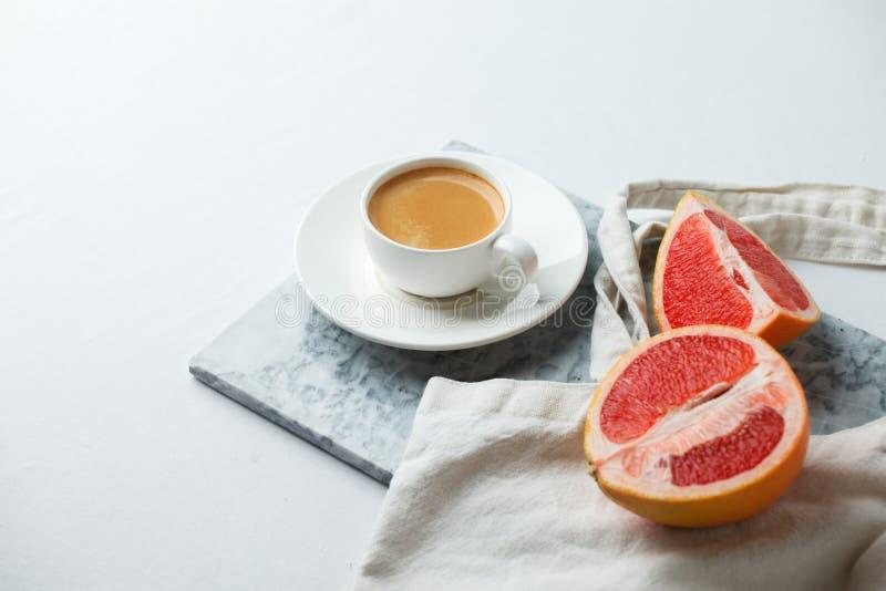 Concepto elegante del desayuno - taza de café, pomelo rojo, bolso del tejido en la placa mafble en el fondo blanco, mínimo modern imagenes de archivo