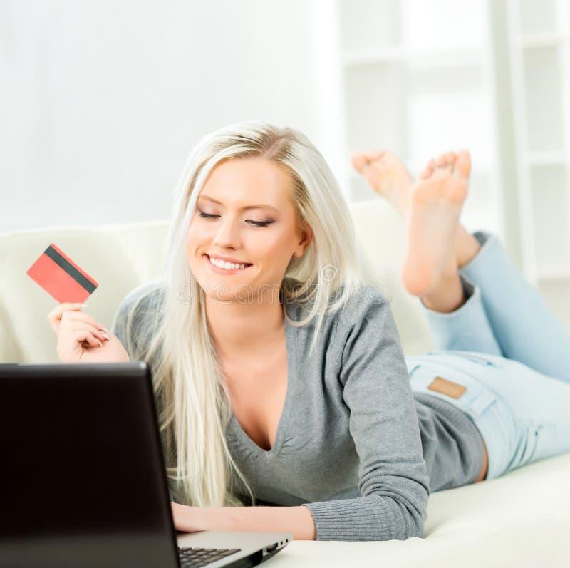 Concepto en línea de las compras Muchacha rubia hermosa con una tarjeta de crédito imagen de archivo
