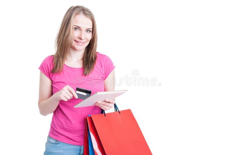Concepto en línea del pago con la mujer joven que hace compras foto de archivo