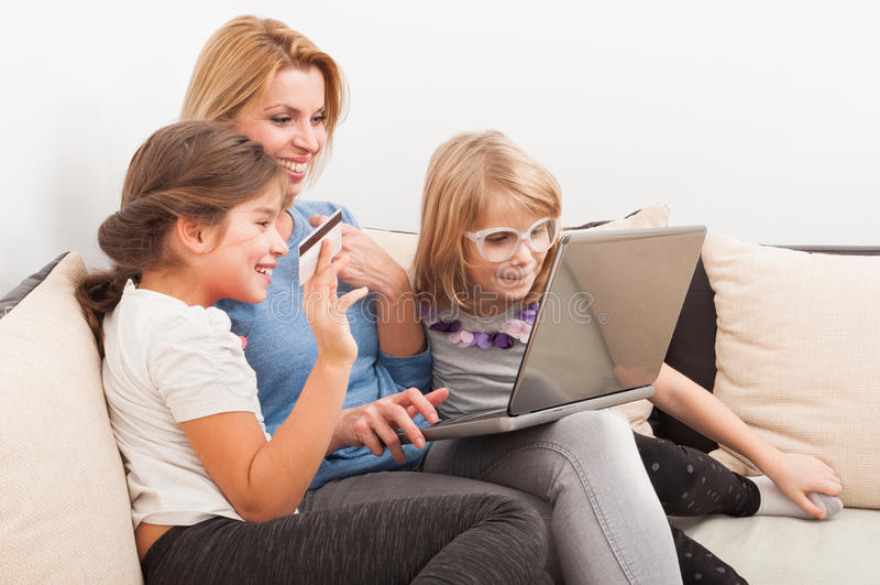 Concepto en línea que hace compras de la familia feliz usando el ordenador portátil y el coche del crédito foto de archivo