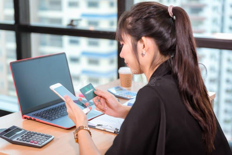 Concepto en línea que hace compras, mano de la mujer del primer que sostiene la tarjeta de crédito mientras que la otra informaci fotografía de archivo