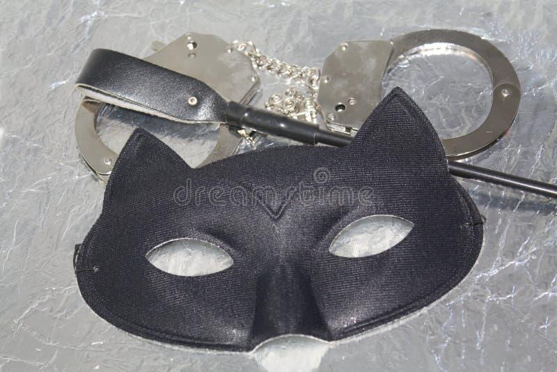 Concepto erótico misterioso de las cosas del placer Máscara de ojo de gato, azote y puños de la mano El jugar del papel del fetic fotos de archivo